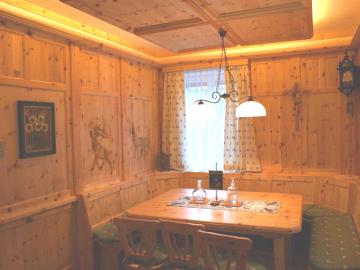 Rustikale Zirbenstube mit Wandverkleidung, Holzdecke mit indirekter Beleuchtung und aufwendige Schnitzerei an den Wänden